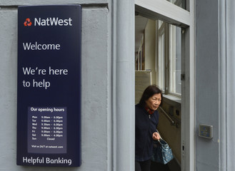 A customer leaves a branch of a NatWest bank in London