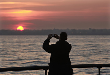 A tourist takes a photo at sunset in New York's Battery Park