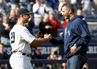 Former New York Yankees pitcher Pettitte shakes hands with catcher Posada after throwing the ceremonial first pitch before Game 2 of the baseball playoffs between the New York Yankees and Detroit Tigers in New York