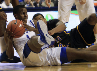 University of Kentucky's Miller fights for the loose ball with Coppin State University's Poole during the second half of play in their NCAA basketball game at Rupp Arena in Lexington