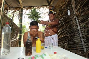 Segundo Asech, a Shuar shaman, performs a cure ritual on Cruz Casent at the Natural Park in Nueva Loja