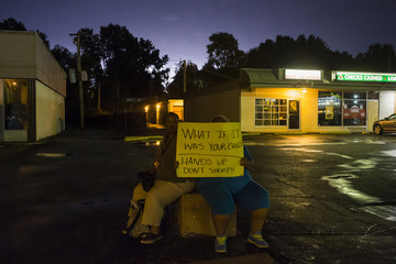 Lightning brightens the sky in the background as women hold a placard while protesting the killing of unarmed black teenager Michael Brown, in Ferguson, Missouri