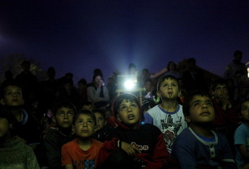 Children watch a cartoon movie, screened at a makeshift camp for migrants and refugees at the Greek-Macedonian border near the village of Idomeni