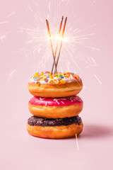 Delicious donuts for birthday on pastel pink background.