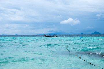 Wooden long tail boat on turquoise sea