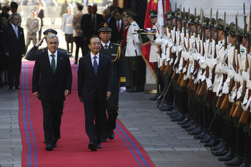 Chile's President Pinera and China's Premier Wen walk past an honour guard at the Presidential Palace at Santiago