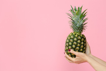 female hands holding pineapple on pink background