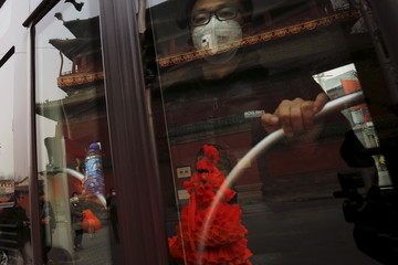 A man wearing a protective mask looks from inside a bus as Chinese artist Kong Ning walks in her costume made of hundreds of orange plastic blowing horns during her art performance raising awareness of the hazardous smog in a historical part of Beijing