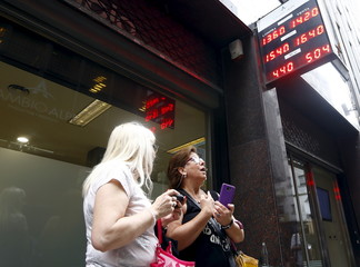 Women look at currency exchange rates board at a money exchange in Buenos Aires' financial district