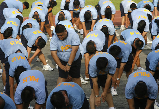 Police officers stretch during their Weight Loss Management Program at Camp Crame in Quezon City Metro Manila