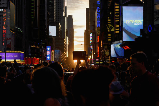 "A person takes a photo with a tablet as the sun sets over Manhattan aligned exactly with the streets in a phenomenon known as ""Manhattanhenge\"