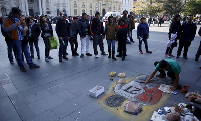 A man draws on the sidewalk a chalk painting of Chile's soccer player Jara and Uruguay's Cavani on the sidewalk in Santiago