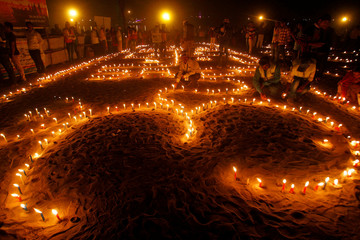 Devotees light candles at the banks of the Ganga river on the occasion of the annual Hindu festival of 'Karthik Purnima' or full moon night, in Allahabad