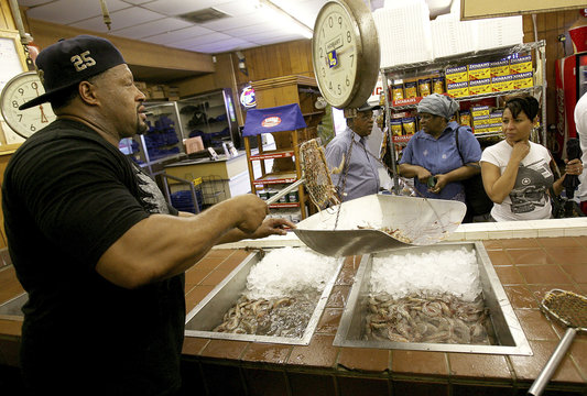 Bruce Peters at Deanie's Seafood weighs shrimp for a customer in Metairie, Louisiana