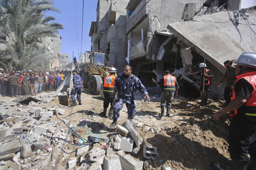 Palestinian policemen take charge as members of the civil defense search for bodies at a house, which police said was destroyed in Israeli air strikes, in Khan Younis