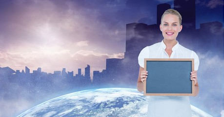 Businesswoman holding blank slate with globe and buildings in background