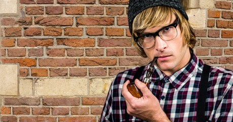 Hipster smoking pipe against brick wall