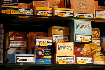 """Packages of small cigars are displyed on sale by a tobacconist with the health warning """"Smoking Kills"""",  as part of anti-smoking legislation in a French 'Tabac' in Paris"""