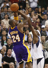 Lakers guard Bryant shoots against Mavericks forward Howard during their NBA basketball game in Dallas