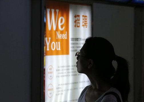 A job seeker looks at a job advertisement board at a Beijing talent service centre