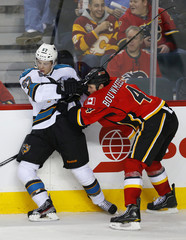 Calgary Flames' Bouwmeester pins San Jose Sharks' Wingels against the boards during their NHL hockey game in Calgary