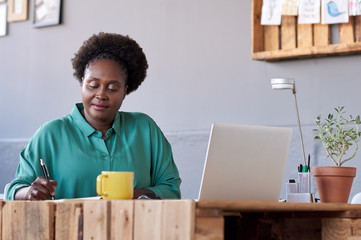 African entrepreneur writing in a notebook at her office desk