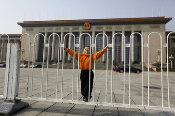 A boy poses for a photo in front of the Great Hall of the People, the venue of the upcoming 18th National Congress of the Communist Party of China, in Beijing
