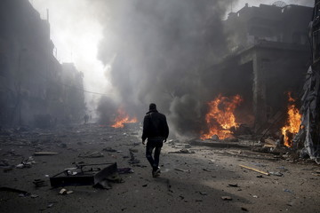 A man inspects a site hit by what activists said were airstrikes by forces loyal to Syria's President Bashar al-Assad, in the Douma neighborhood of Damascus, Syria