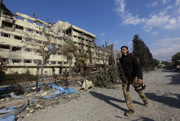 A member of the Iraqi rapid response forces walks past a hospital damaged by clashes during a battle between Iraqi forces and Islamic State militants in the Wahda district of eastern Mosul, Iraq