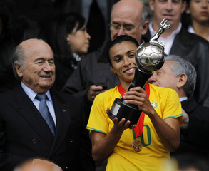 Brazil's Marta, flanked by FIFA President Joseph Blatter, looks at the trophy after winning the final match at the South American Women's Championships in Quito