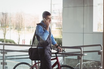 Businessman talking on mobile phone while pushing his bicycle