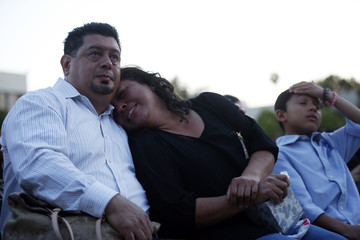 Veronica, mother of high school senior Adrian Castro, who was killed in last Thursday's bus crash, listens to speakers at a candlelight vigil in his memory at El Monte High School in El Monte