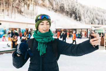 The attractive girl in winter clothes takes a selfie. She has flicked out tongue language and winks. Around her there are a lot of people.