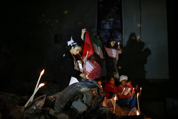 Palestinian children hold candles atop the rubble of a house, which witnesses said was destroyed in an Israeli air strike during an eight-conflict in Gaza