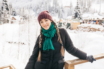 The beautiful girl during a winter time. On her a blue jacket, a menthol scarf and a lilac cap. The girl lovely smiles. Her hair are braided in braids.