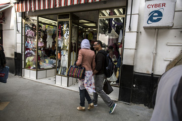 A couple walks past a shop in Algiers