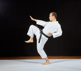 A man in karategi beats a kick leg on a black background