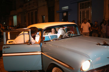 Guests take pictures inside a vintage car as they arrive for a dinner with U.S. pop star and singer Madonna, in front of a restaurant in downtown Havana, Cuba