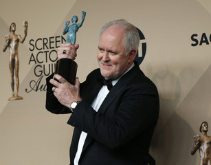 """John Lithgow poses with the award he won for Outstanding Performance by a Male Actor in a Drama Series for his role in """"The Crown"""" backstage at the 23rd Screen Actors Guild Awards in Los Angeles"""