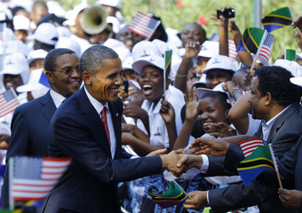U.S. President Obama and Tanzania's President Kikwete greet Tanzanians during an official welcoming ceremony in Dar Es Salaam
