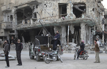 Free Syrian Army fighters and civilians look at the sky as they stand past damaged buildings in Deir al-Zor, eastern Syria