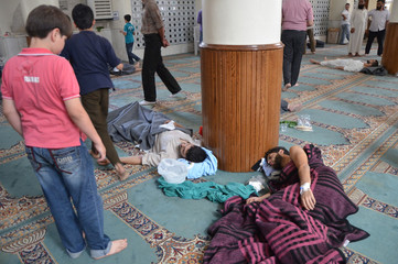 A boy looks at survivors from what activists say is a gas attack resting inside a mosque in the Duma neighbourhood of Damascus