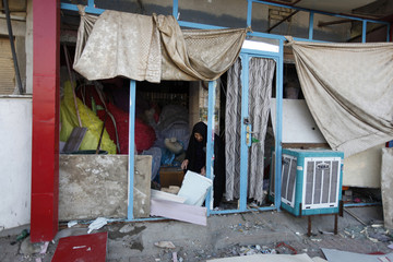 A woman picks up wreckage from her shop which was damaged during Tuesday's bomb attack in Baghdad's Sadr City