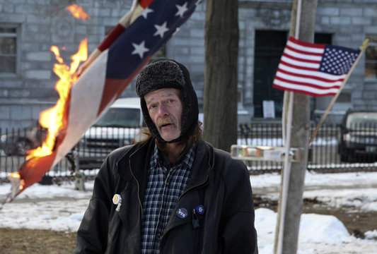 Occupy Maine protester Harry Brown burns an American flag to dispose it as the eviction deadline for the encampment approaches in Lincoln Park, in Portland
