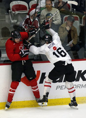 Reinhart gets hit by Ritchie during the red-white team game at the Team Canada selection camp in Calgary
