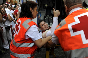 An unidentified runner gestures while being attended by medical services following the first running of the bulls of the San Fermin festival in Pamplona