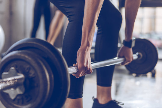 Close-up partial view of sportswoman lifting barbell at gym workout