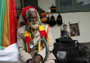 Member of the Rastafarian movement sits on a sidewalk while waiting for the unveiling of a statue of late reggae legend Bob Marley in Kingston