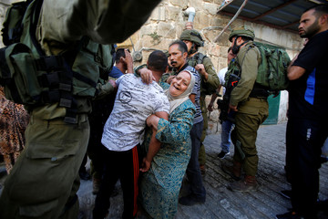 A Palestinian woman cries as she holds her relative before he was detained by Israeli soldiers during a searching raid by Israeli troops in the West Bank city of Hebron