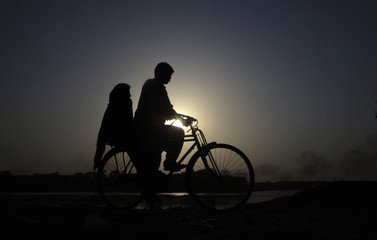 A couple is silhouetted against the setting sun as they ride a bicycle to their residence near the banks of the Ravi river in Lahore